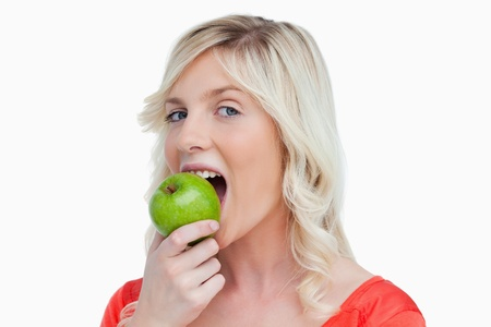 Attractive woman eating a delicious green apple against a white background photo