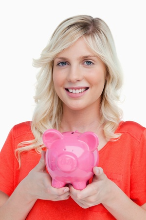 Smiling teenage girl holding a pink piggy bank against a white background photo