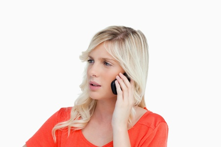 Serious and attractive young woman talking on the phone while looking on the side Stock Photo - 13676639