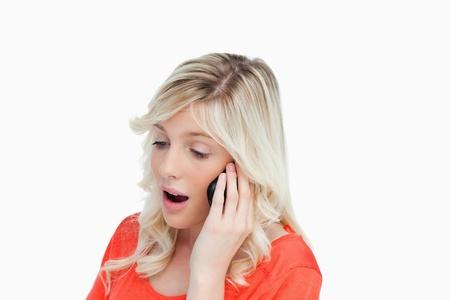 energetically: Woman energetically speaking with a mobile phone against a white background Stock Photo