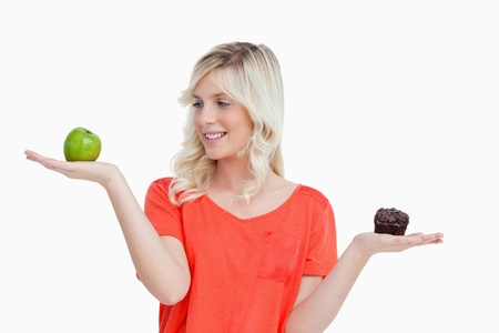 health choice: Young woman imitating a balance to choose between a fruit and chocolate