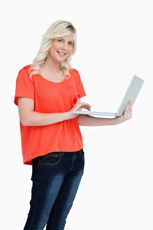Smiling and beautiful woman looking at the camera while holding a new laptop photo