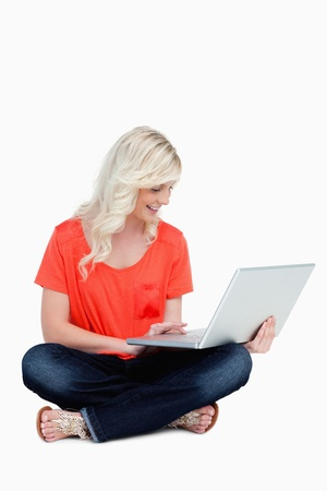 Young woman sitting cross-legged with her laptop against a white background photo