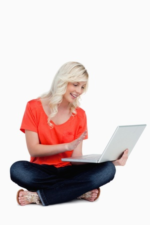 Beautiful fair-haired woman waving her right hand in front of her new grey laptop photo