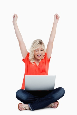 Successful attractive young woman raising her arms in front of her laptop photo