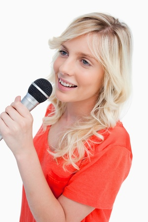 Smiling woman singing with a microphone against a white background photo