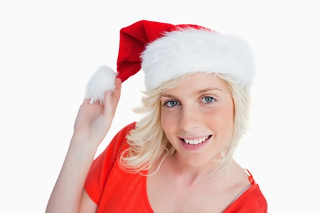 Young woman holding the pompom of her Christmas hat against a white background Stock Photo