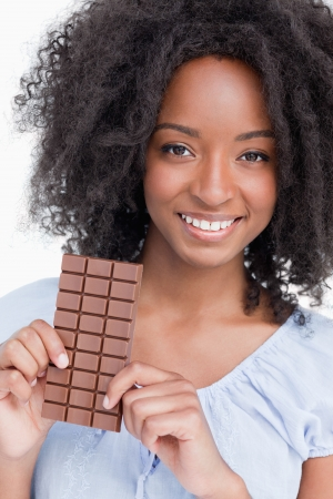 Smiling woman with curly hair holding a chocolate bar against a white background photo