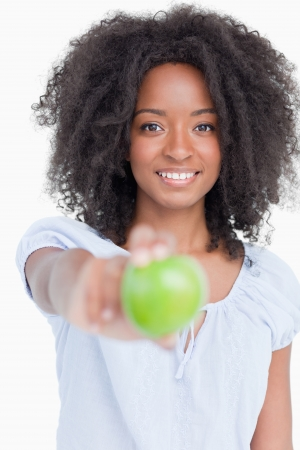 Smiling young woman holding a delicious green apple against a white background Stock Photo - 13671295