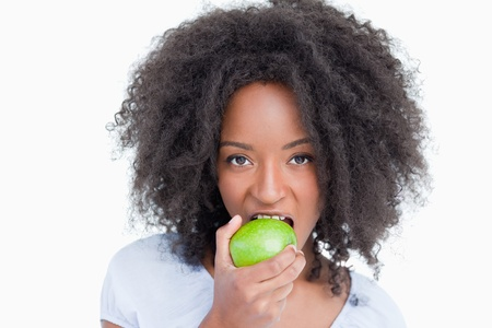 Young woman looking straight at the camera and eating a delicious green apple Stock Photo - 13671762