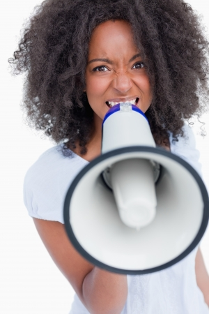 Young woman speaking loud into a megaphone against a white background photo