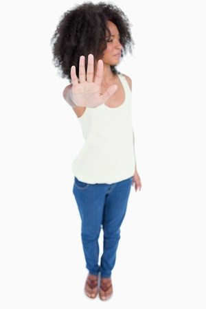Young woman with curly hair looking on the side while showing the hand stop sign photo