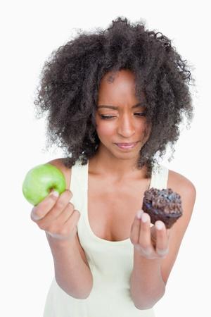 dudando: Mujer joven que duda entre un panecillo y una manzana sobre un fondo blanco