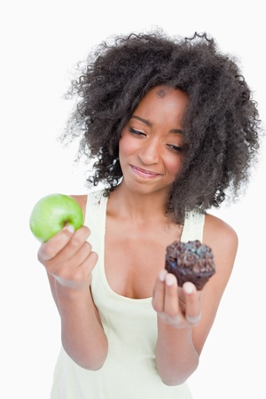 hesitating: Young woman hardly hesitating between a chocolate muffin and a green apple