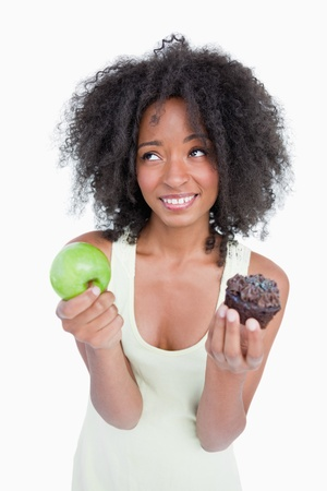 Woman looking up to ask for help to choose between a fruit and a chocolate muffin photo