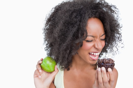 Young woman on the point to eat a chocolate muffin against a white background Stock Photo - 13671863