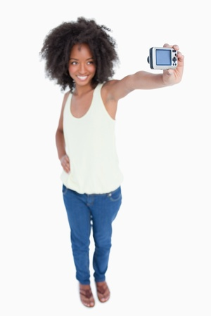 Young smiling woman holding her digital camera against a white background photo
