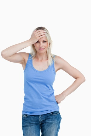 Blonde woman placing her hand on her forehead against a white background