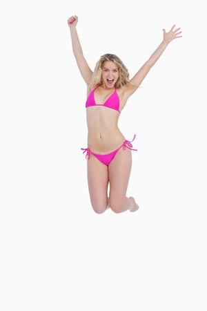 energetically: Blonde woman in swimsuit energetically jumping against a white background