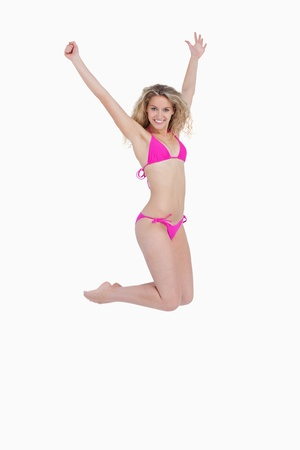 Attractive woman wearing a pink swimsuit while jumping against a white background photo