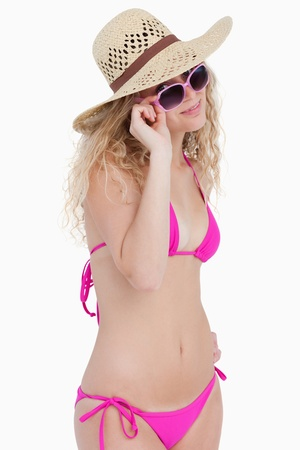 Attractive blonde teenager looking over her sunglasses against a white background photo