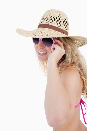 Smiling teenage putting on her sunglasses against a white background photo