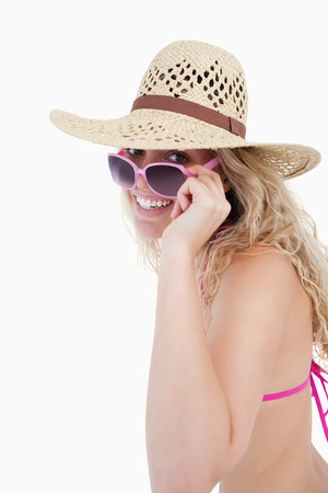 Smiling teenager in a swimsuit looking over her sunglasses against a white background photo