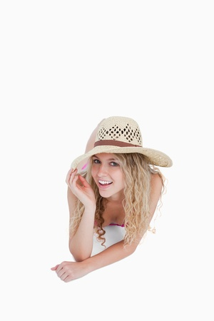 Smiling teenager lying down while holding her hat brim against a white background photo