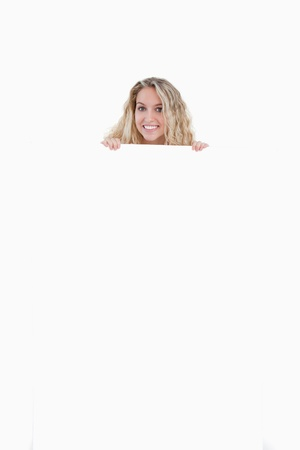 Young woman hiding her body behind a blank poster against a white background Stock Photo - 13666708