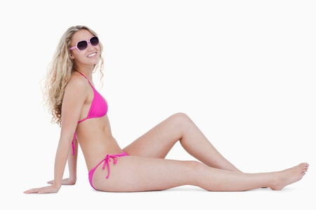 Attractive woman sitting down wearing sunglasses against a white background photo