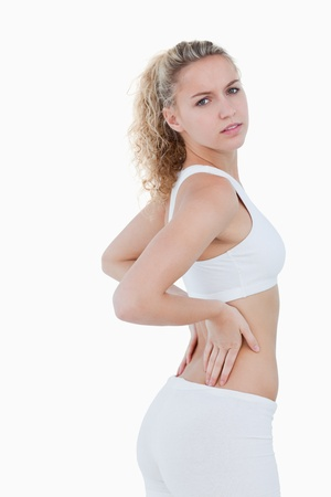 Young attractive woman touching her back against a white background photo
