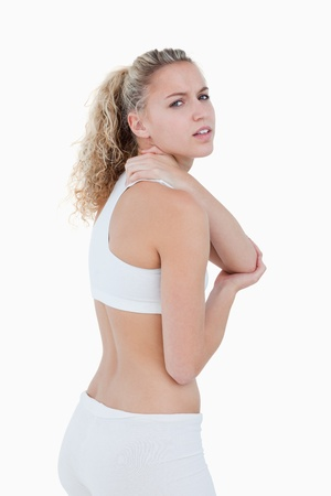 Young woman showing a pain in her shoulder against a white background photo