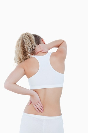 Blonde woman touching her painful neck and back against a white background photo
