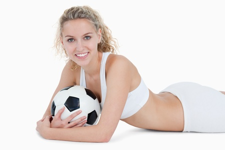 Smiling teenager lying down with a football in her arms against a white background photo