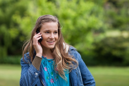 Smiling teenage girl looking towards the side while calling with her mobile phone photo