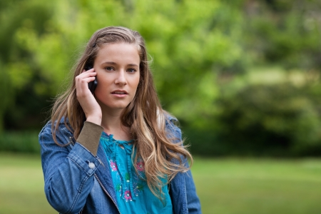 Young serious woman talking on the phone while standing in the countryside photo
