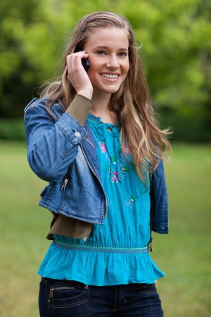 Smiling and relaxed teenager using her cellphone while standing in the countryside photo