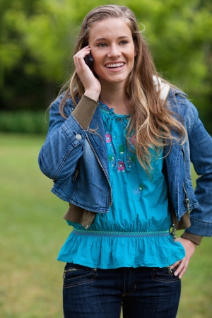 Smiling teenage girl talking with her mobile phone while standing in the countryside photo