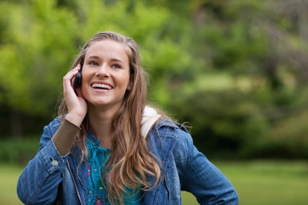 Teenager using her cellphone while showing a beaming smile photo