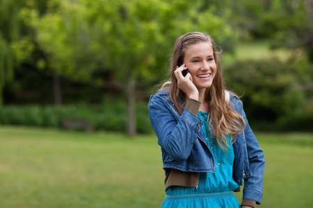 Teenage girl standing in the countryside while using her mobile phone photo