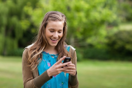 Happy teenage girl receiving a text on her mobile phone while standing in a park photo