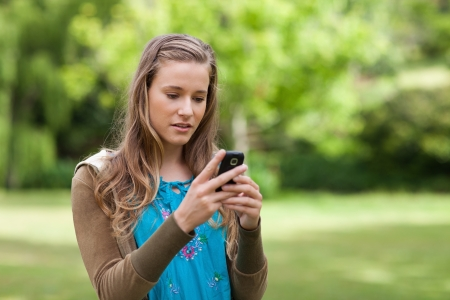 Serious teenager sending a text with her cellphone while standing in a park photo