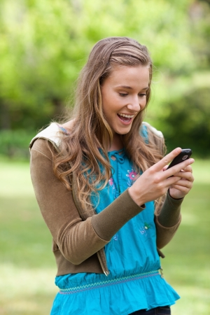 Teenager receiving a surprising text on her mobile phone while standing in a park photo