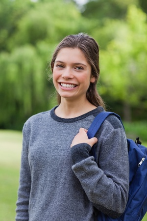 hair tied: Young relaxed girl smiling while standing up with hair tied and carrying her backpack
