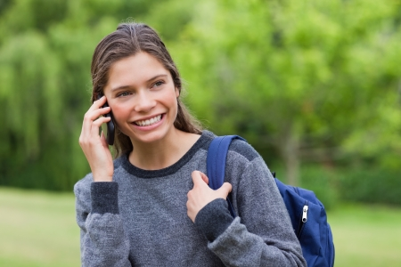 Young smiling girl standing in a park while looking away and talking on the phone photo