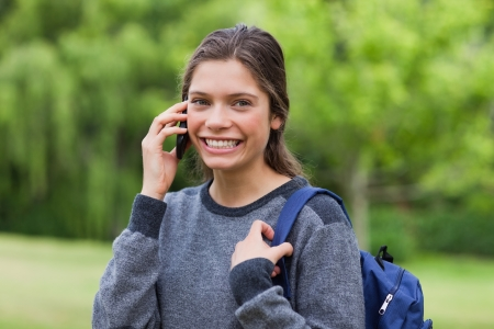 Young happy adult using her mobile phone while standing upright in the countryside photo