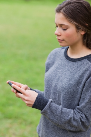 Young serious girl sending a text with her mobile phone while standing in a park Stock Photo - 13668398