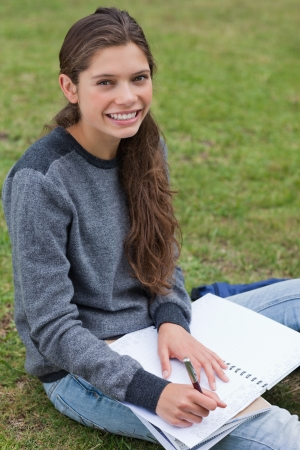 Smiling young woman writing on her notebook while sitting on the grass photo