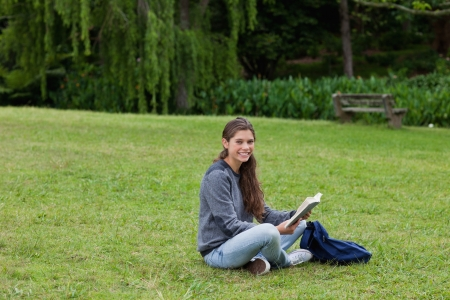 Smiling young adult reading a book while sitting cross-legged on the grass in a park photo