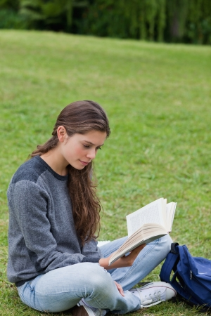 crossing legs: Young woman sitting on the grass while crossing her legs and reading a book